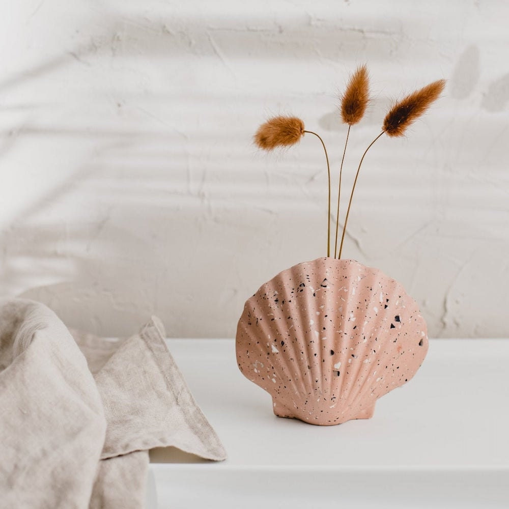A pink terrazzo vase from Badger & Birch, shaped like a seashell