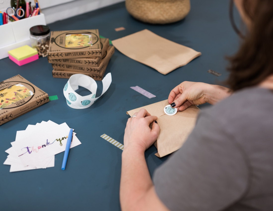 Liz packages an embroidery hoop kit for shipment, adding a Cozy Blue sticker to the outside
