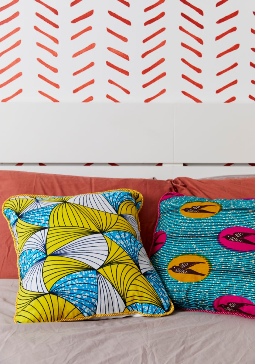 A set of decorative throw pillow covers (styled on a bed, with inserts) from Bespoke Binny