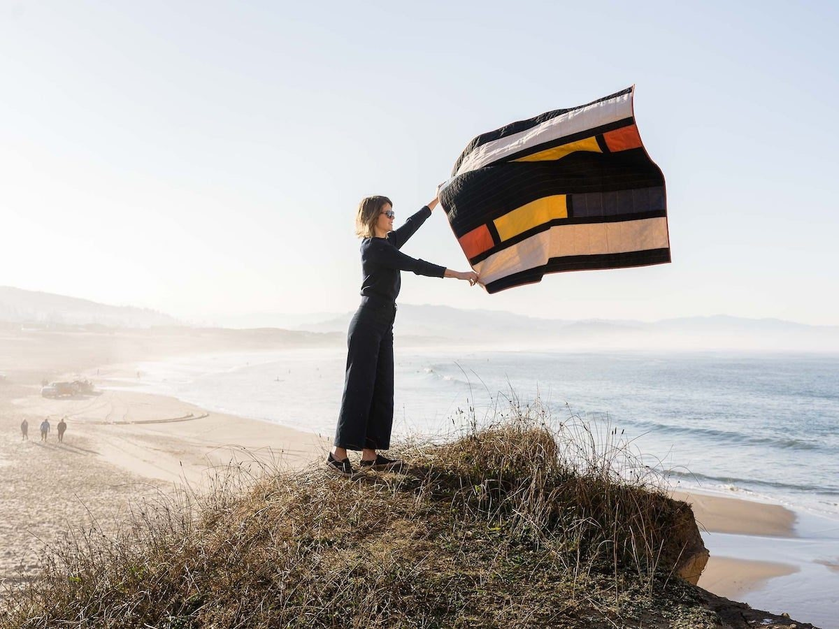A woman overlooking a beach holds up a color-blocked quilt from Vacilando Quilting, letting it float in the wind