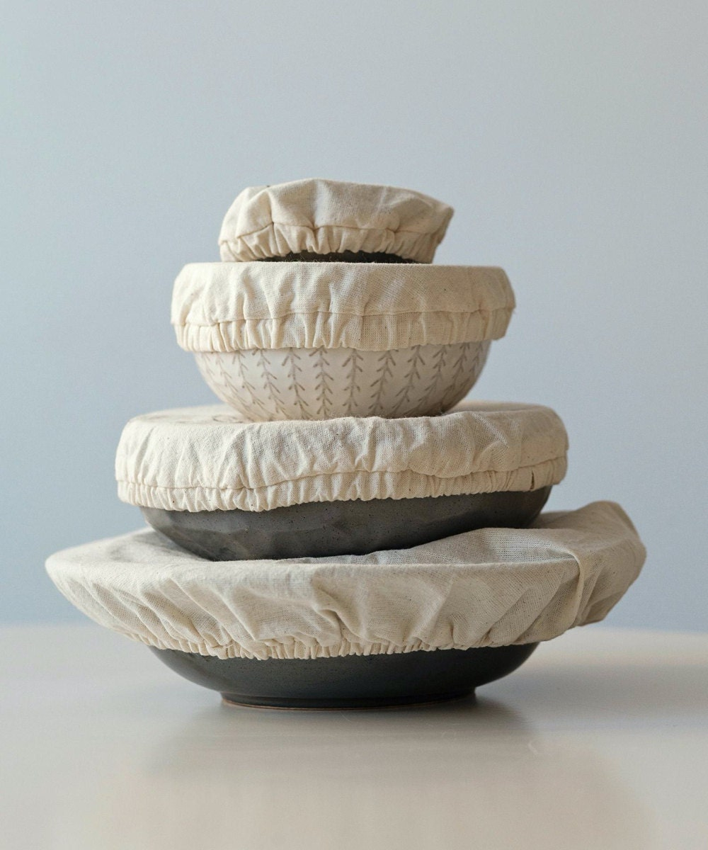 A set of natural-colored reusable linen bowl covers shown covering bowls of various sizes.