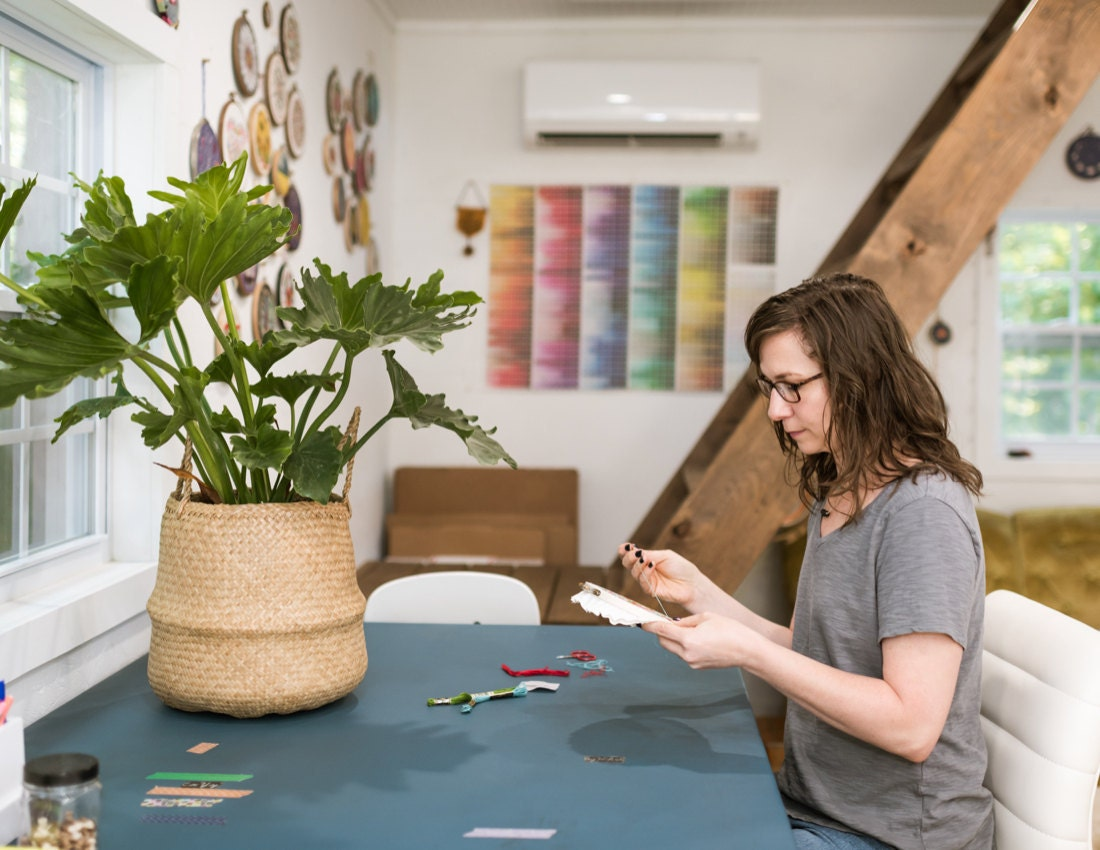Liz at her desk, working on an embroidery hoop