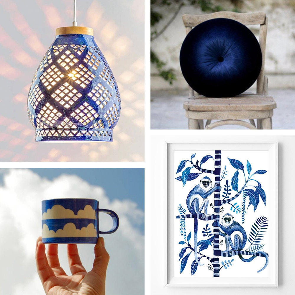 A collage of sapphire-colored items for the home, including a pendant light, a velvet pillow, a monkey art print, and a blue mug with clouds on it