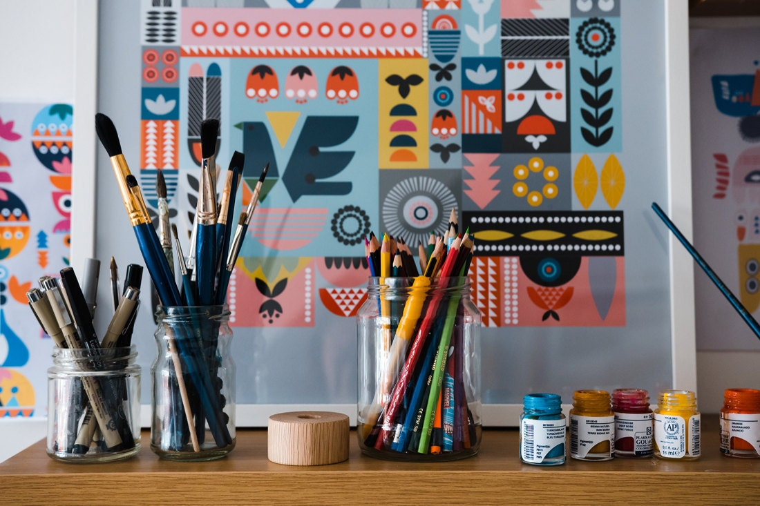 Tatiana's neatly organized supply shelf, stocked with colorful pencils, pens, brushes, and paints.