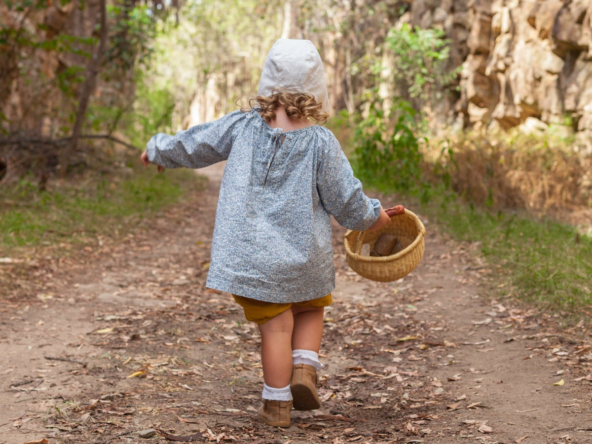 Child at play wearing an écolier kids smock and bonnet