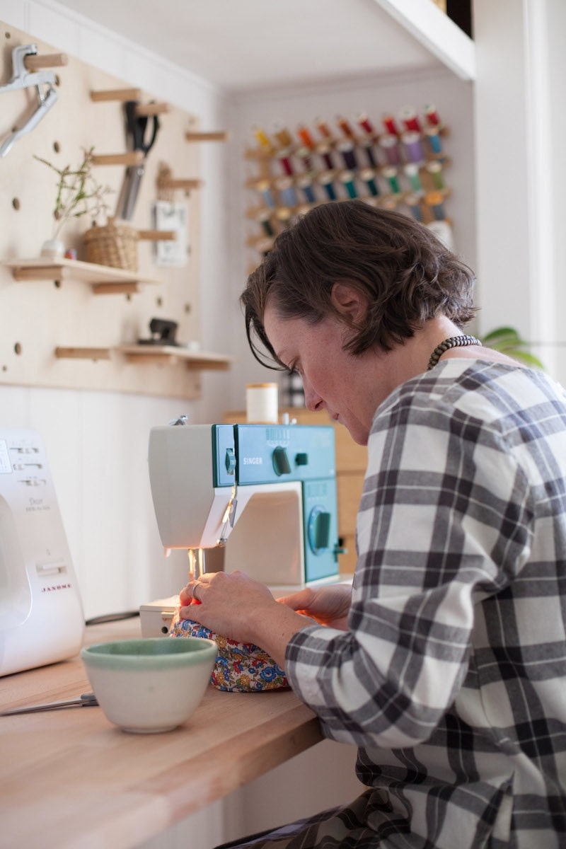 Madeline Bell sewing at her workbench