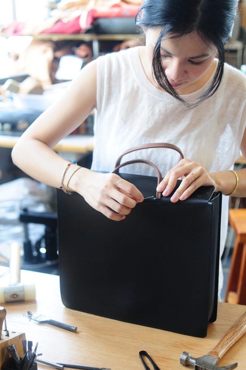 Joe sewing the handle on a leather bag