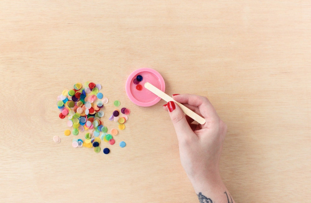 Rachel pushes individual pieces of confetti into her resin mold with a wooden stick.