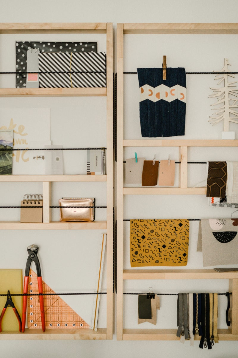 Eda's neatly organized studio shelves (filled with fabric swatches, tools, notebooks, and art) double as an inspiration board