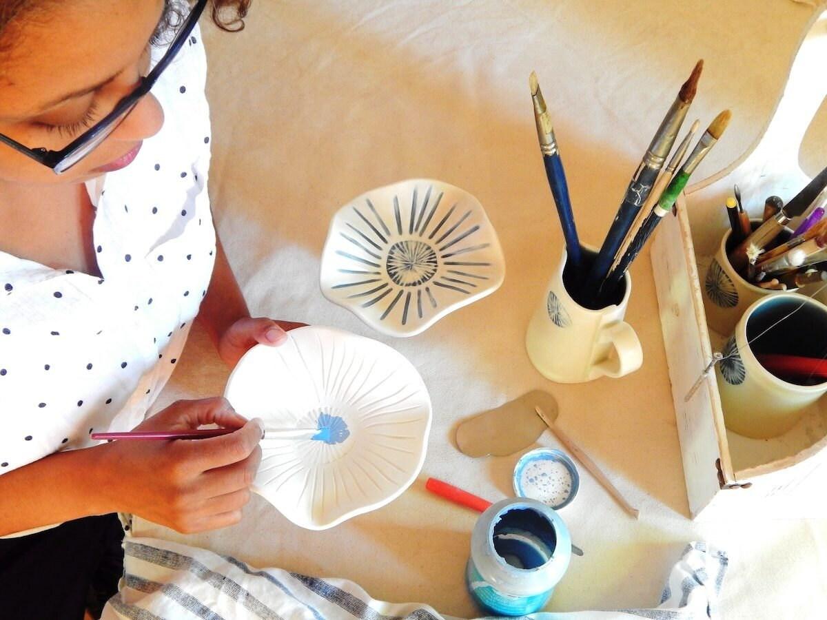 Edith paints a ceramic tea light holder