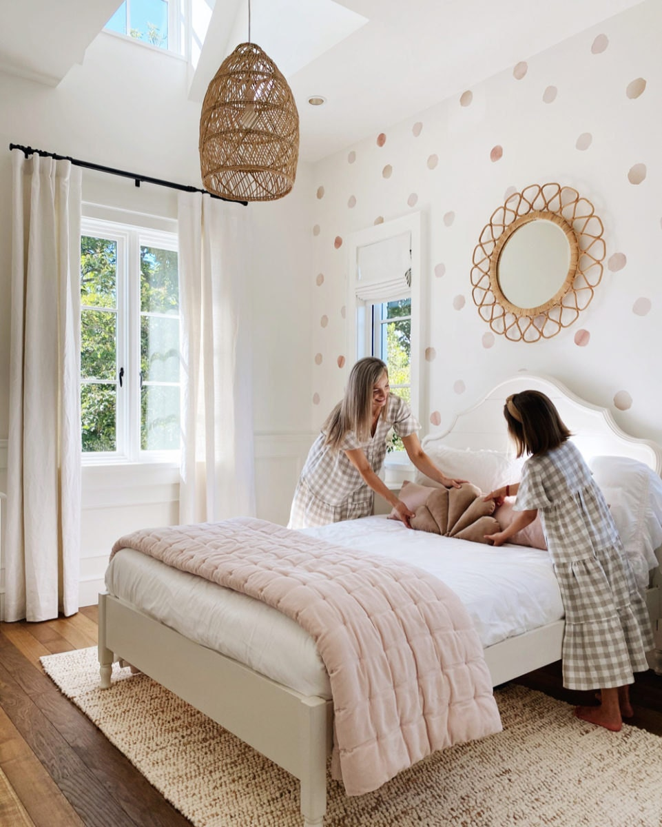 Kristine and her daughter make the bed, adding a shell throw pillow to the top.