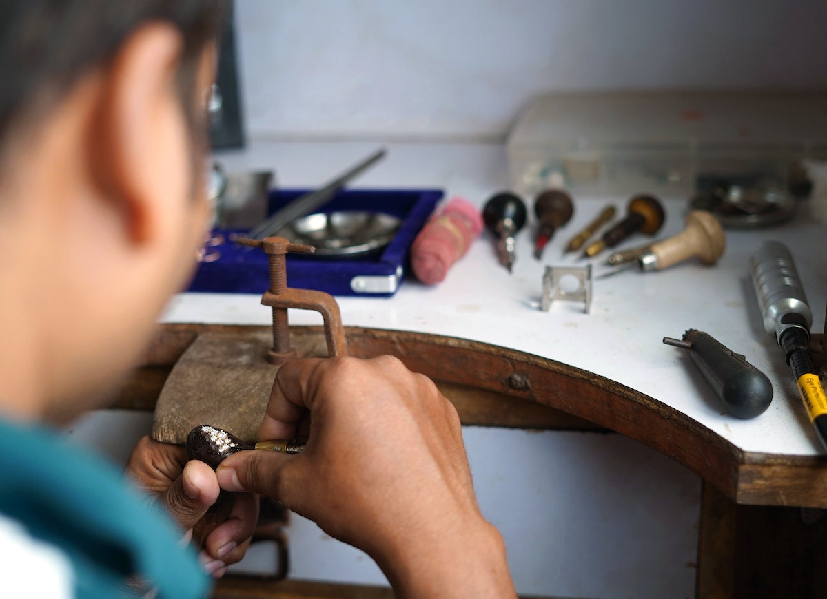 A member of the Abhika Jewels team sets a diamond ring at his workbench