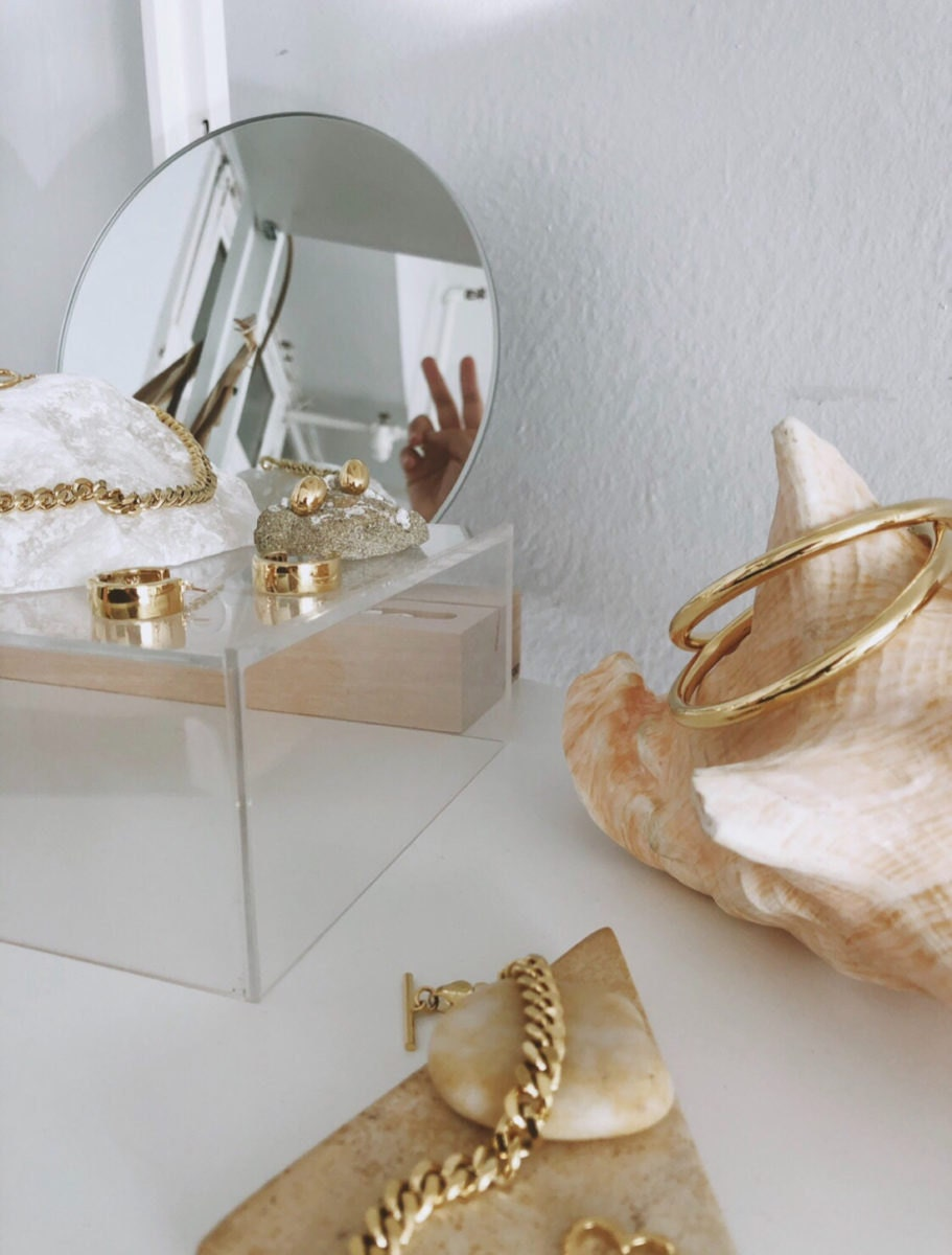 An assortment of gold earrings, necklaces, and bracelets from the Foe & Dear collection