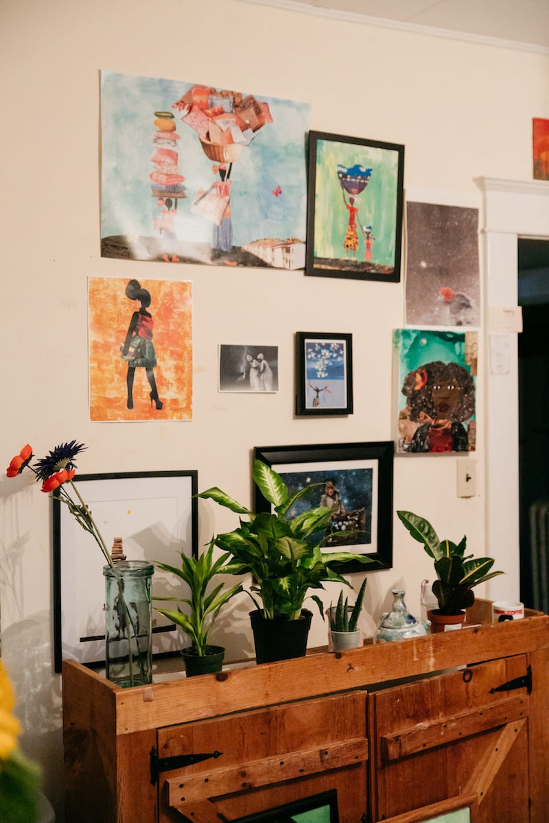 Mirlande's dining room studio wall, decorated with her colorful prints