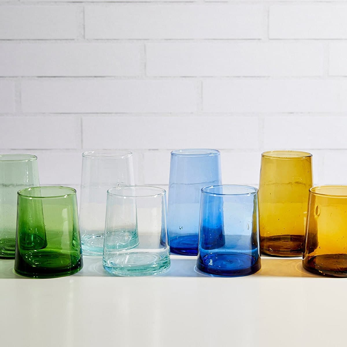 Eight glasses in green, clear, blue, and amber
