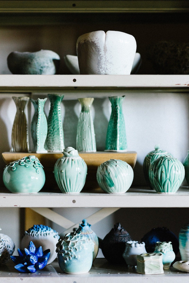 Finishes vessels and vases from Echo of Nature sit on a shelf in Yumiko's studio