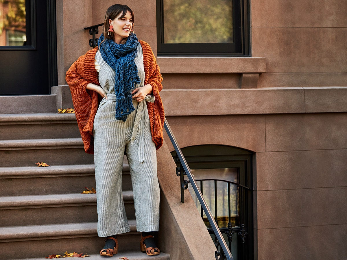 Woman standing on stoop stairs wearing a linen jumpsuit, knit cardigan, oversized scarf, and clogs