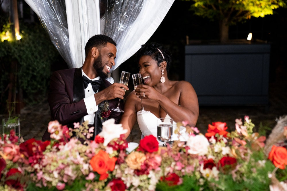 A portrait of Addy and Joel toasting at their sweetheart table on their wedding night.