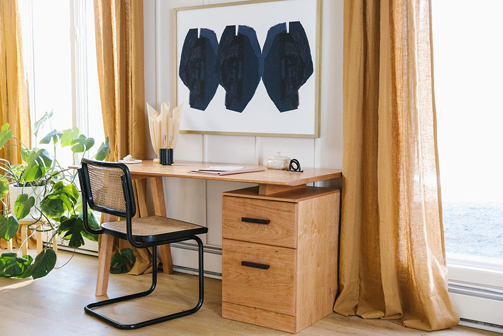 Windows with long amber curtains flank a wooden desk with drawers and a surface that appears to be floating.