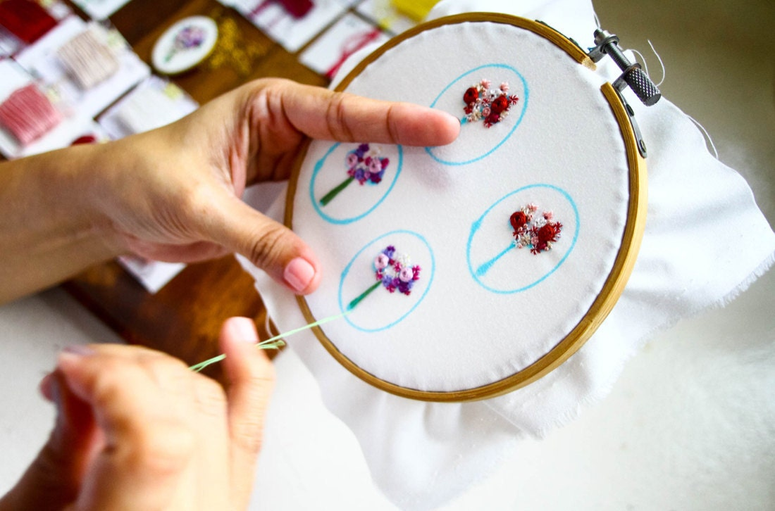 Ruby embroiders four separate jewelry designs on the same piece of fabric stretched over a larger hoop