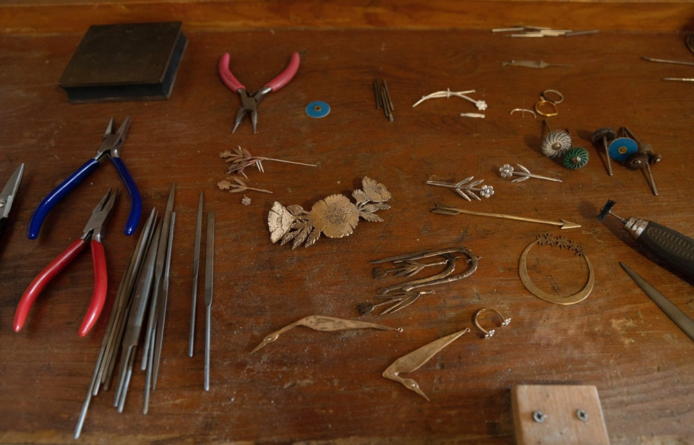 Jieun's workbench scattered with unfinished pieces and jewelry-making tools
