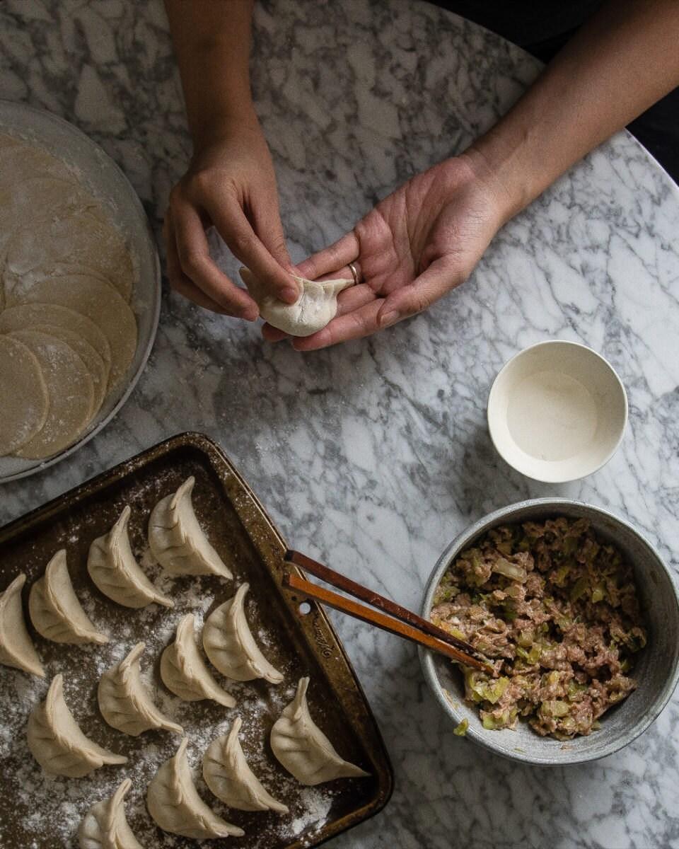 Shaping the filled dough into dumplings