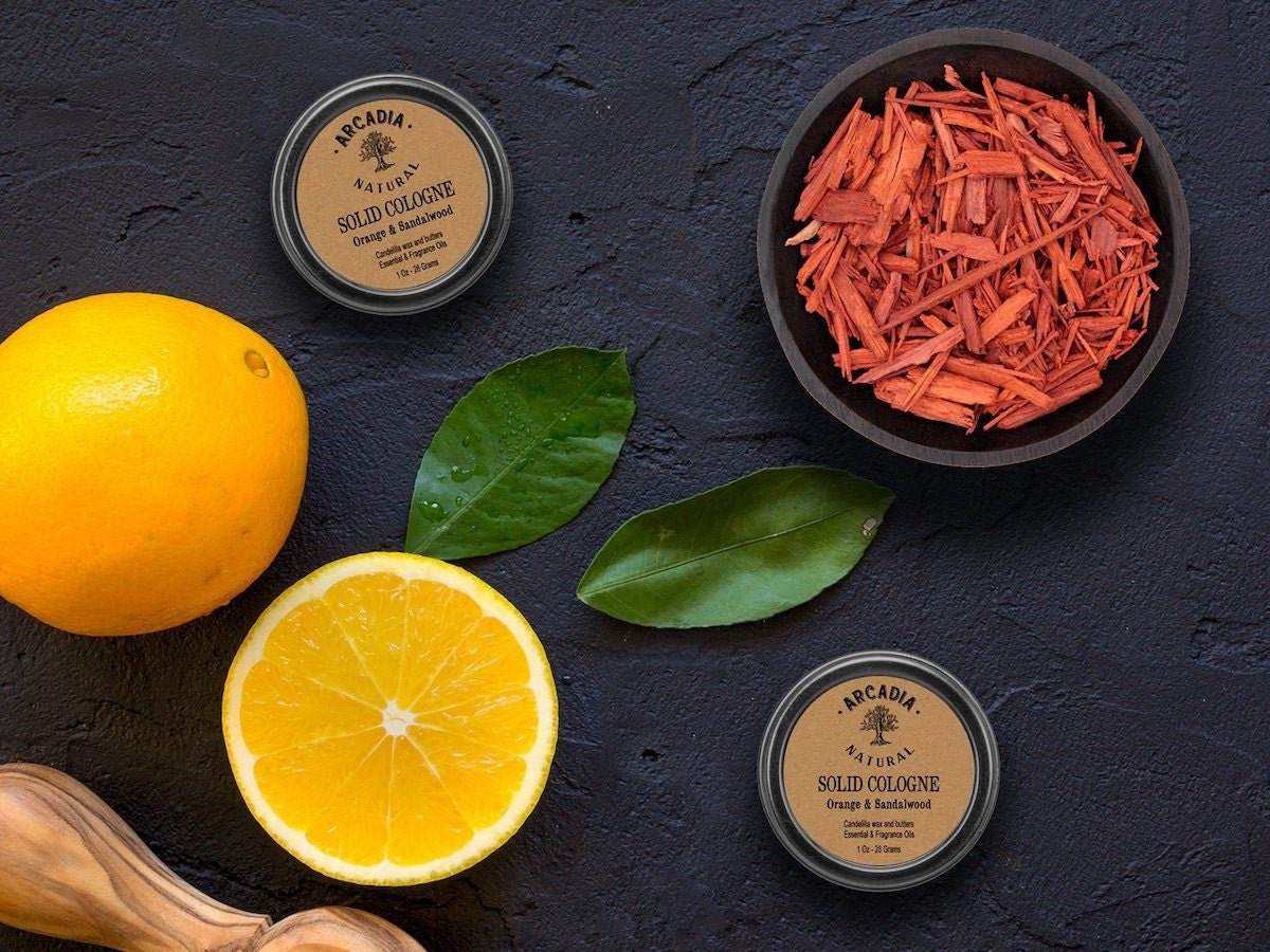Solid cologne displayed on a table with sandalwood chips and oranges.