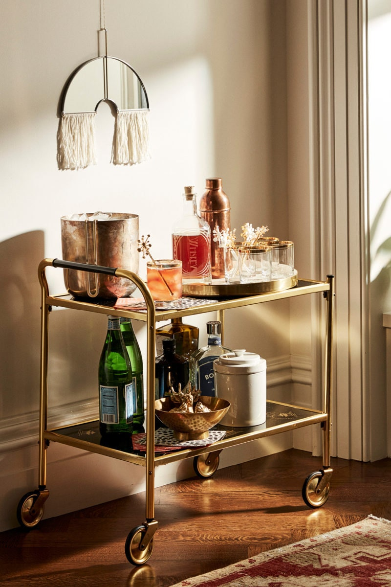 A vintage '60s bar cart featuring a custom spirit decanter, vintage highball glasses, and other cocktail-crafting essentials