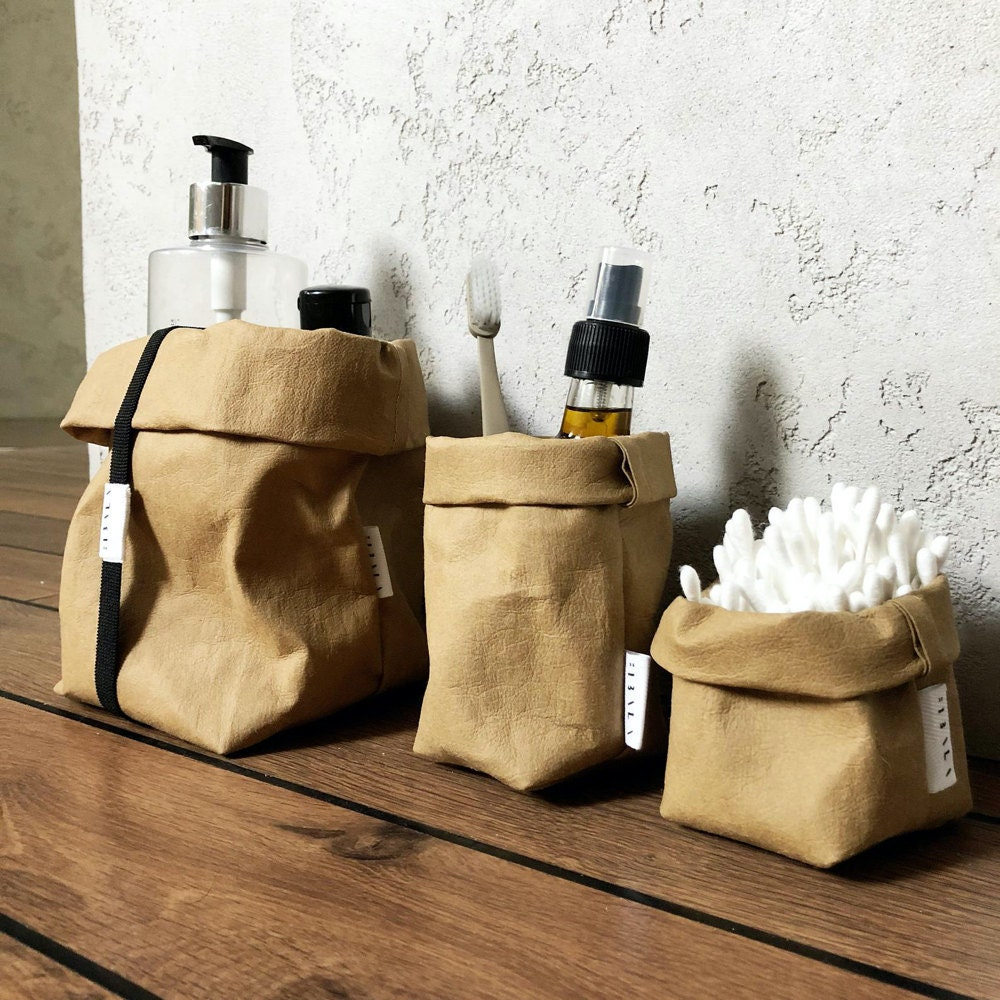 A trio of washable paper market bags in various sizes, shown storing bathroom staples like cotton swabs and toothbrushes.