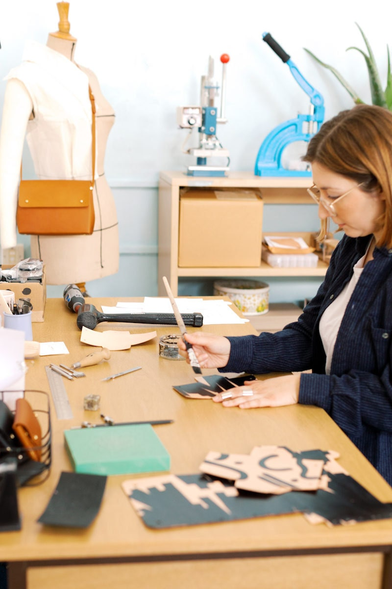 Jessica hand-paints a piece of leather while seated at her desk