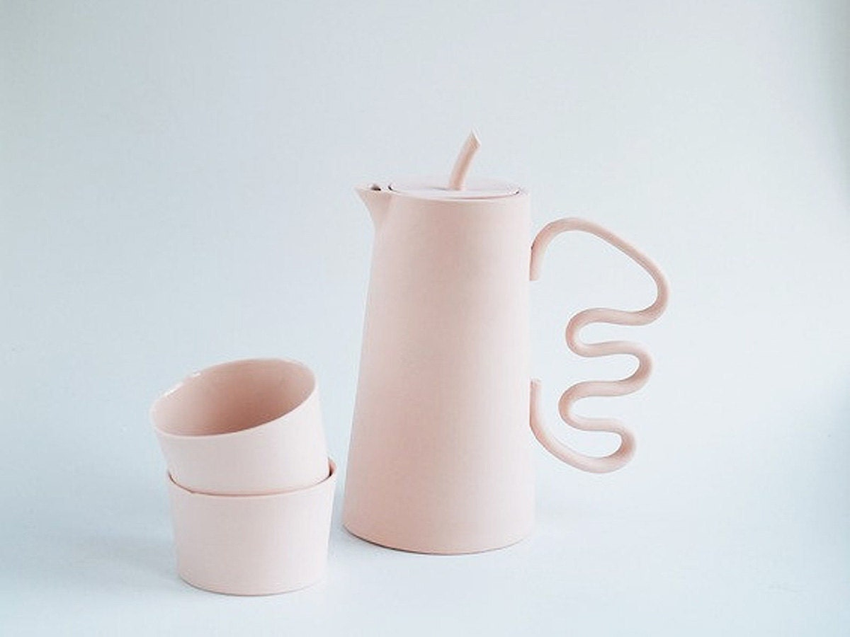 A pink tea set and pitcher with a wavy handle