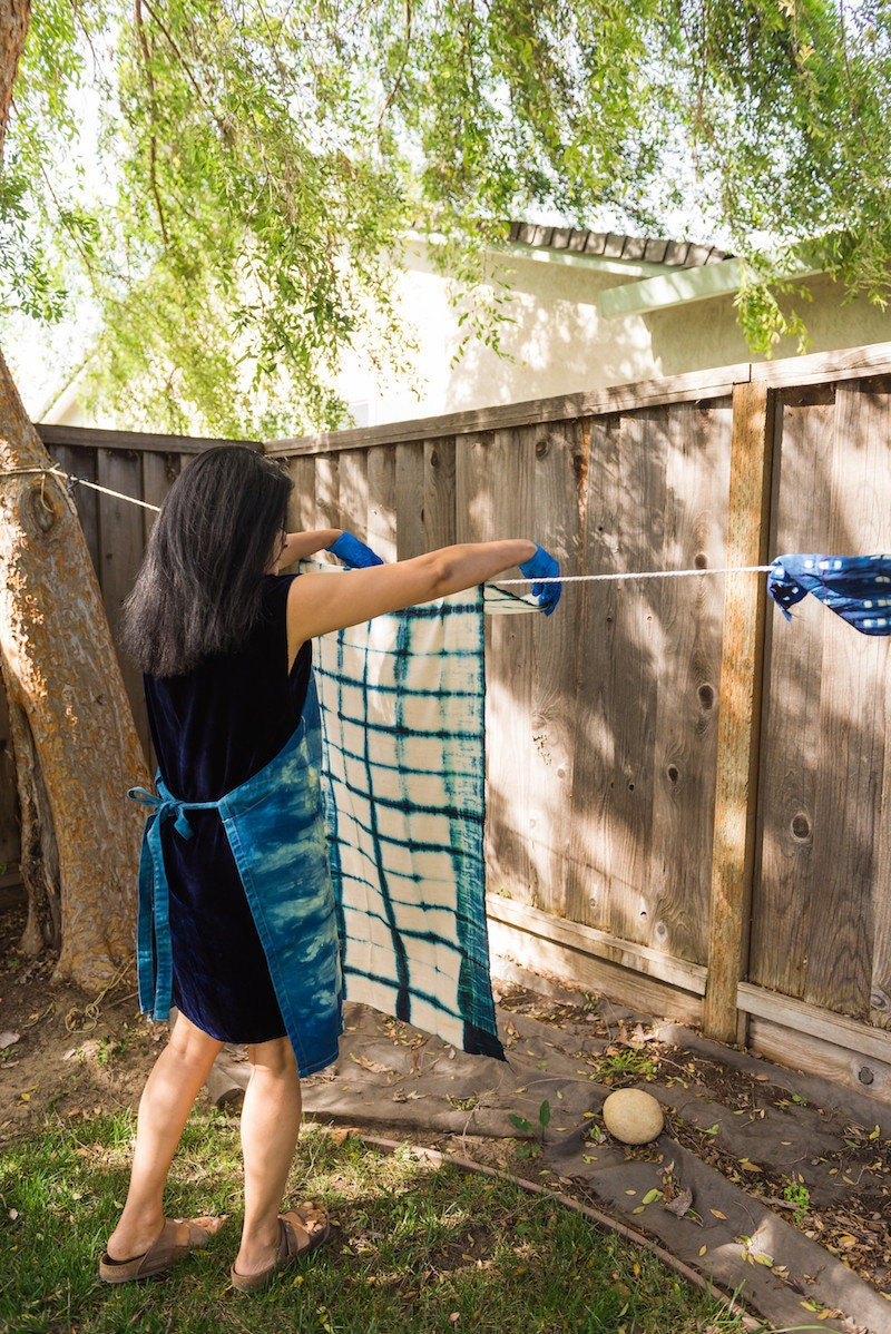 Rajni drapes a just-dyed piece of fabric over a clothesline in her backyard to dry
