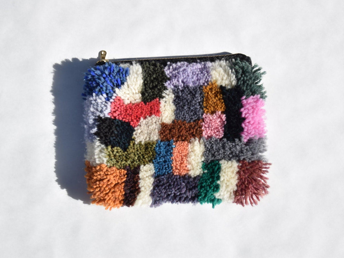 A colorful furry clutch made of yarn against a white background.