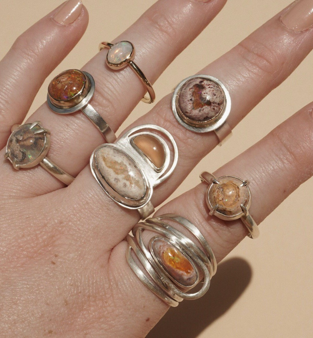 Assorted opal statement rings from Aleishla styled on a hand.