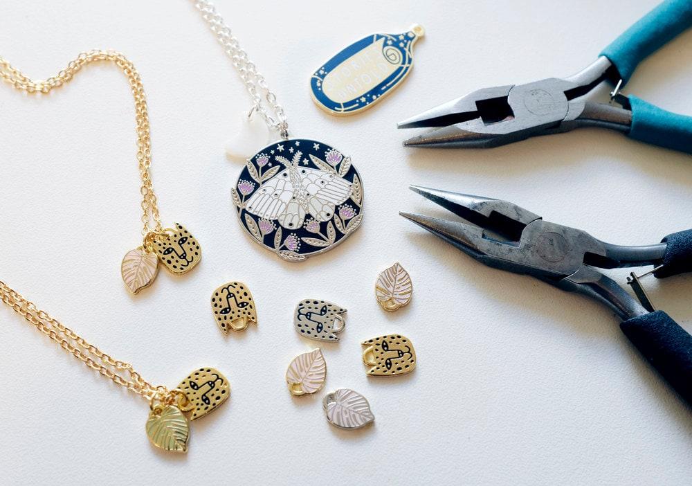 Assorted moth necklace pieces arranged alongside a set of pliers