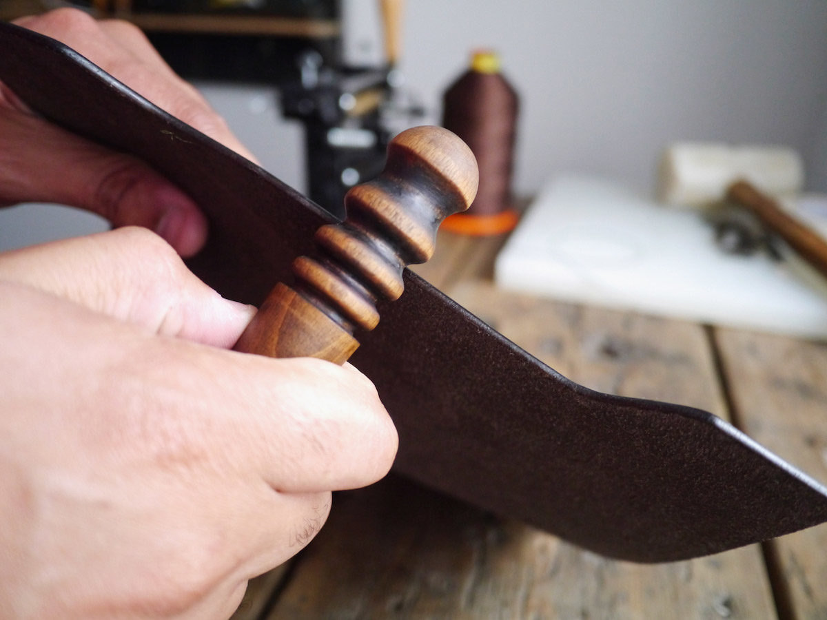 Kingsley works with a piece of leather