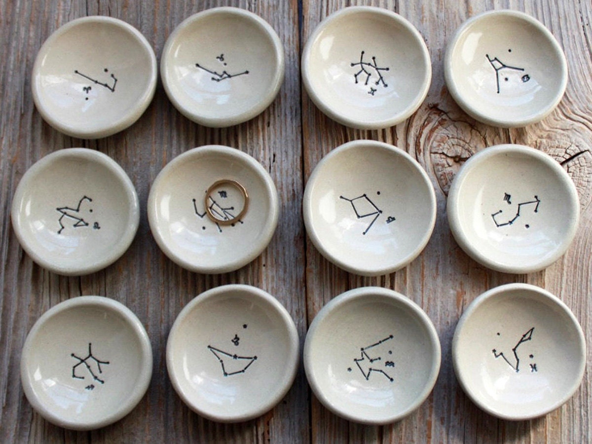 12 astrological ring dishes on a wooden background.