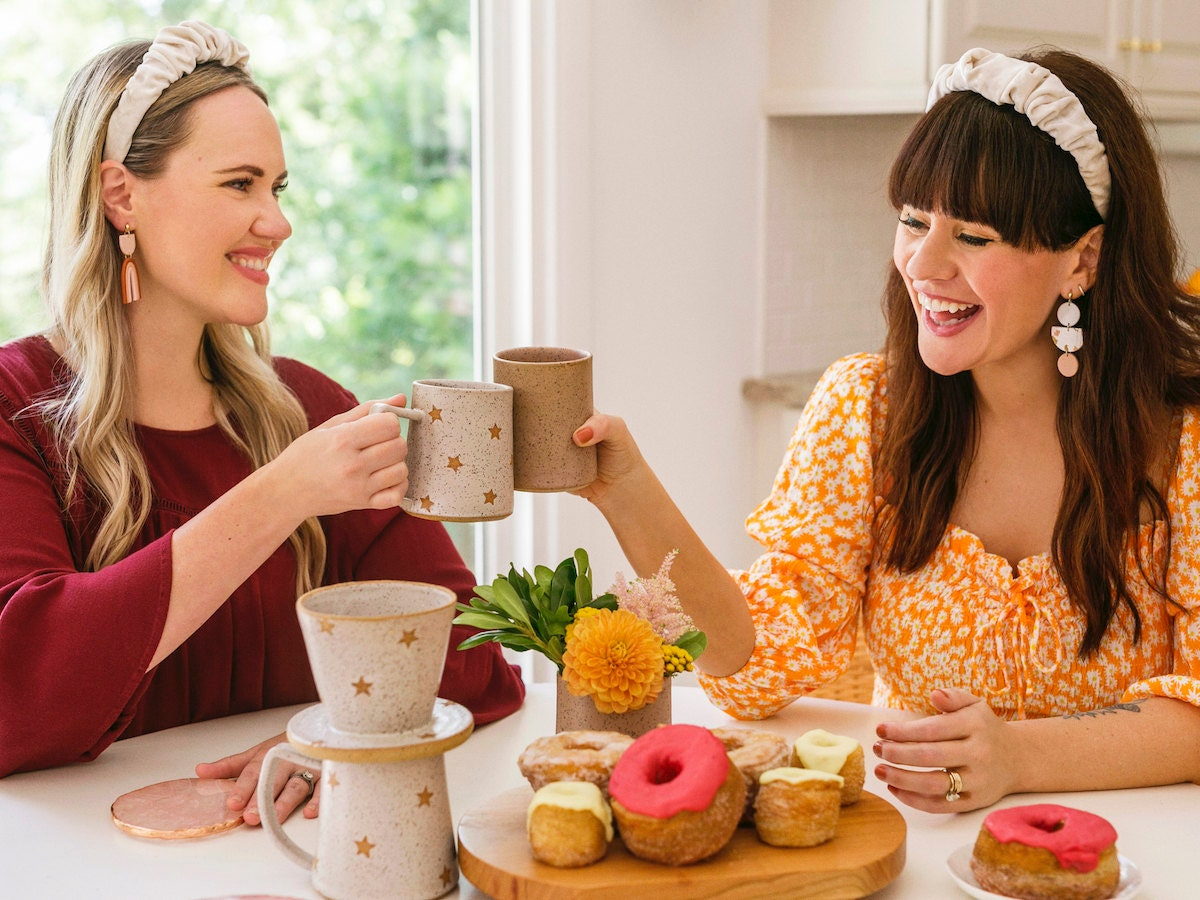 Elsie and Emma cheers with mugs at a kitchen table