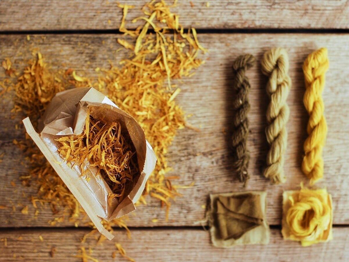 Bag of osage wood chips photographed alongside natural-died yarn skeins