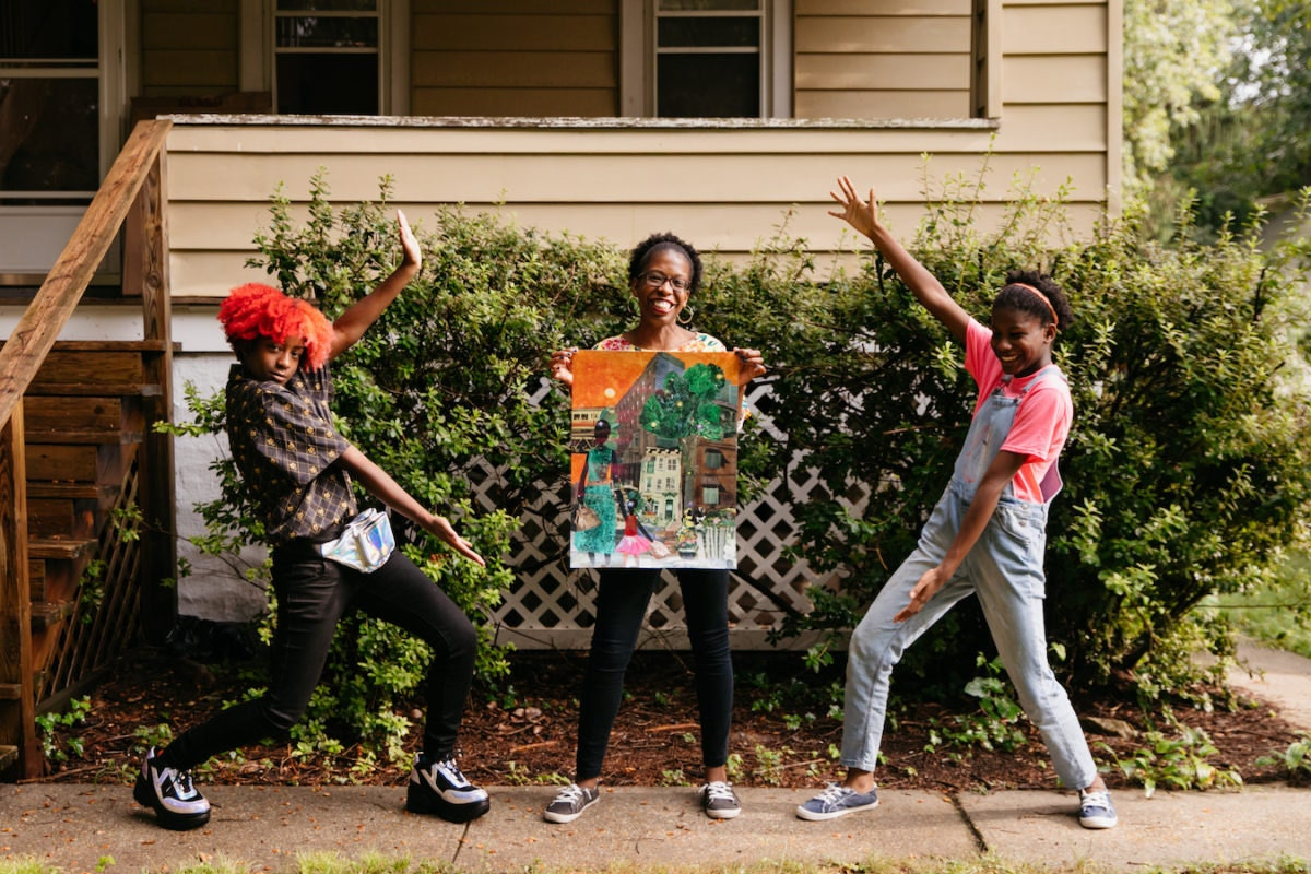 """Mirlande and her daughters pose with a print of """"On Our Way to Ballet Class"""""""