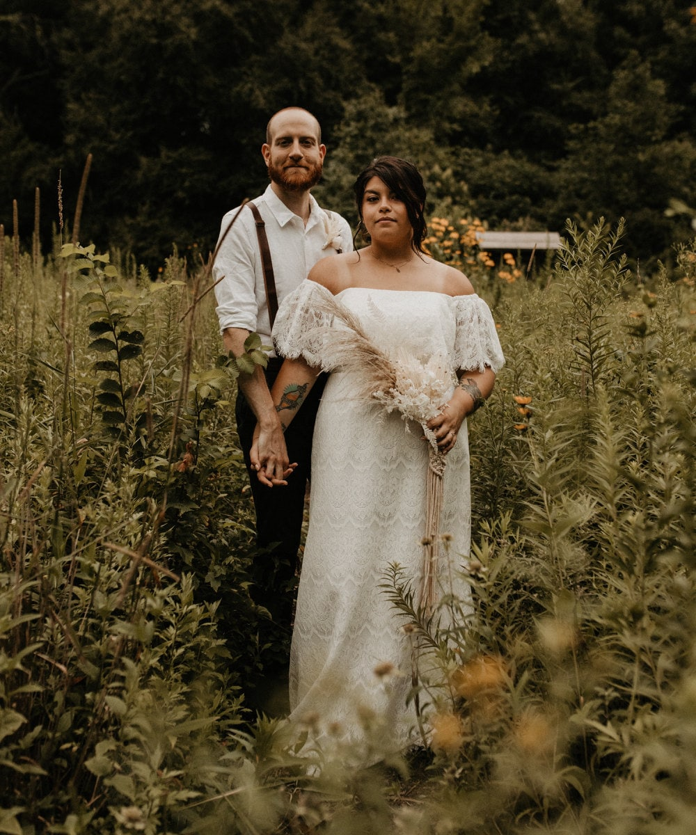 A portrait of Sarah and Chris Schalago standing in a meadow on their wedding day.