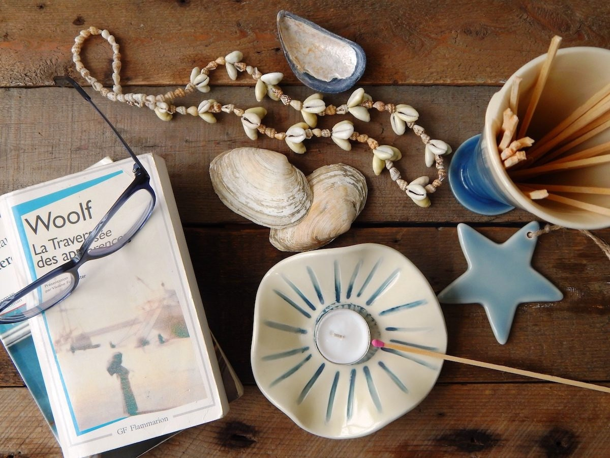 Assorted Lilot Poterie items arranged on a wooden surface with seashells and books