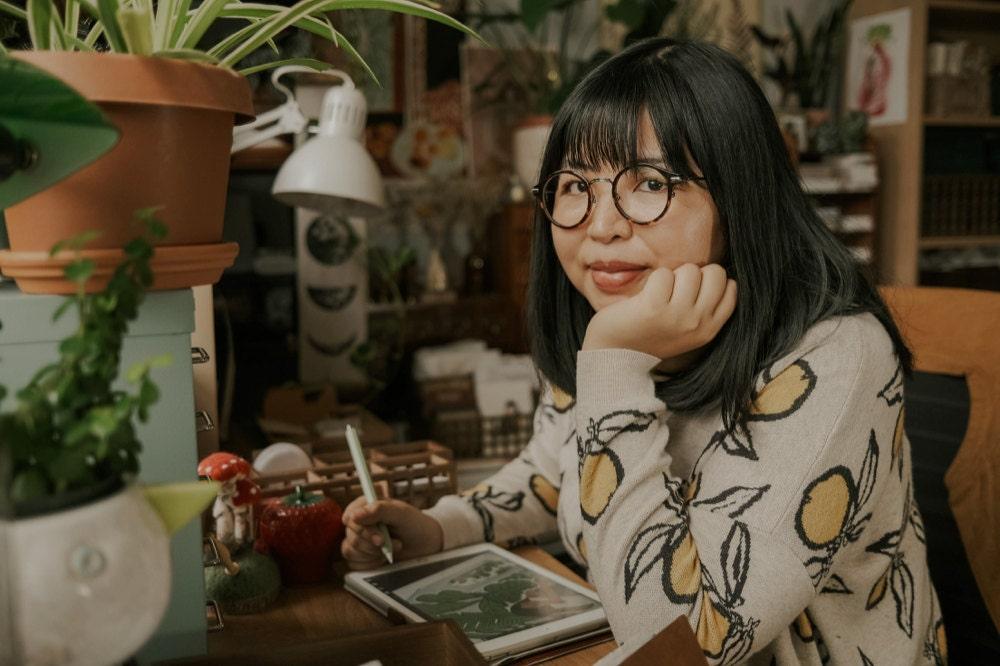 A portrait of illustrator and accessories designer Justine Gilbuena in her New York studio