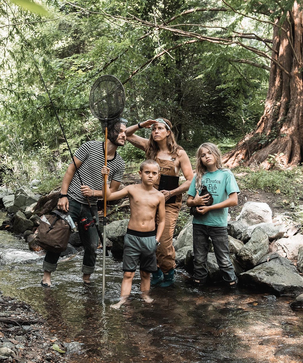 Family portrait of Peg and Awl owners Margaux and Walter Kent and their two children posing playfully out in nature.