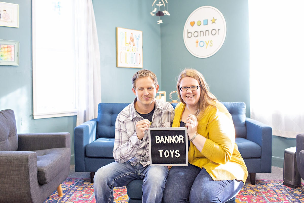 Seated portrait of Bannor Toys proprietors Stacey and Jesse Bannor in their Madrid, Iowa studio headquarters