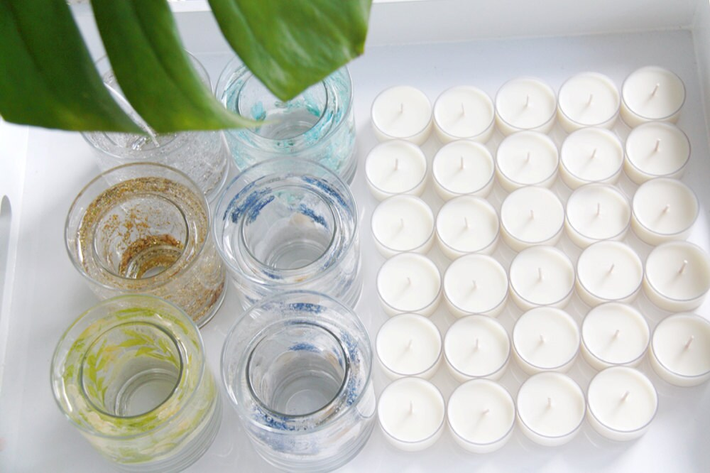 Soy wax tea light candles lined up to be added to decorative glass jars.