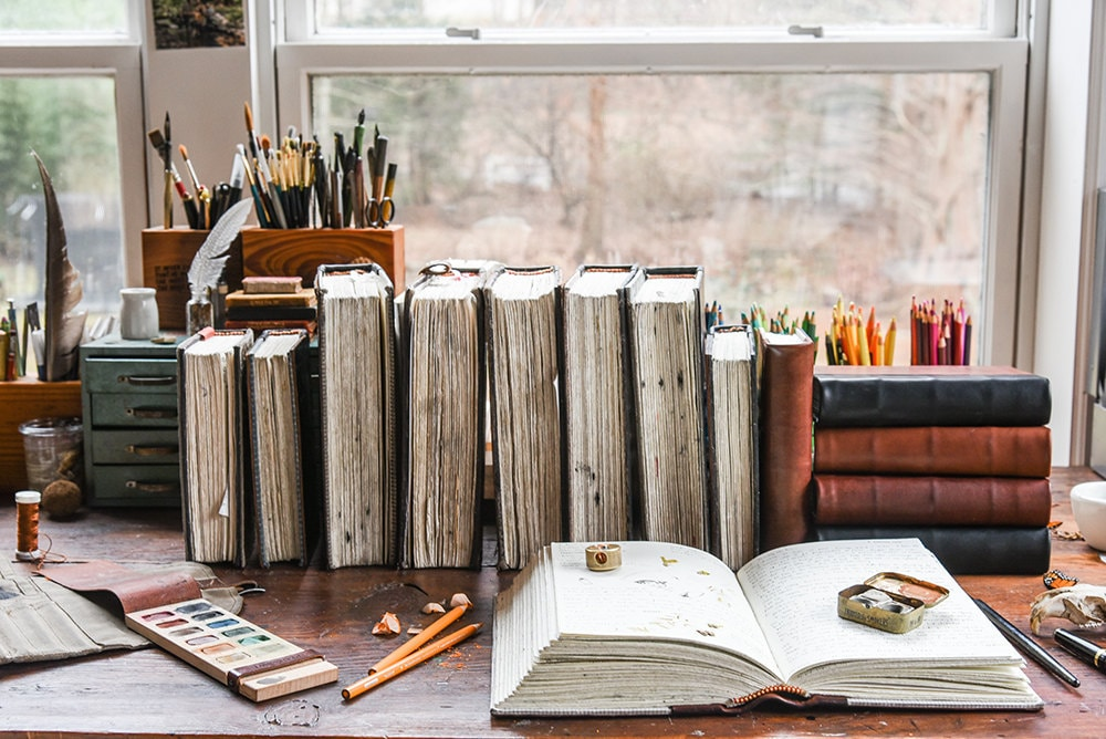 A desk decorated with bound books, desk caddies, and a painter's palette.