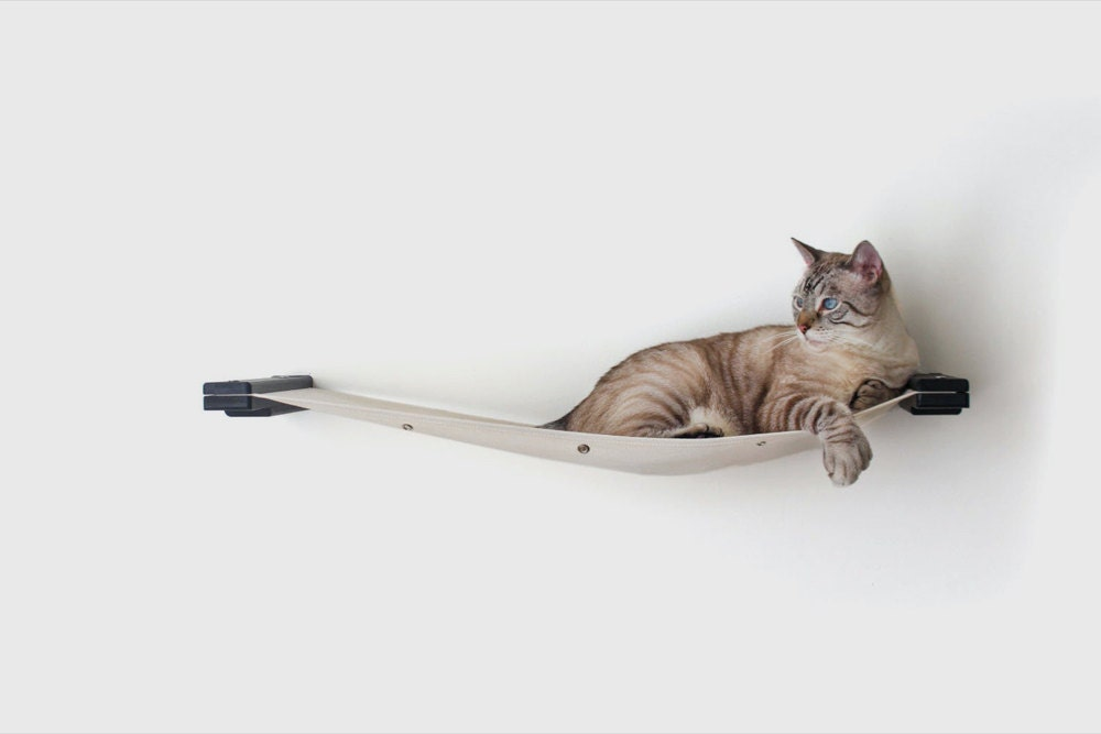 A wall-mounted canvas cat hammock from CatastrophiCreations