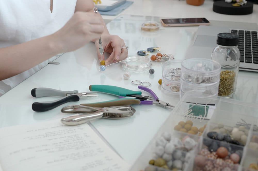 Jessica assembles an earring at her desk.