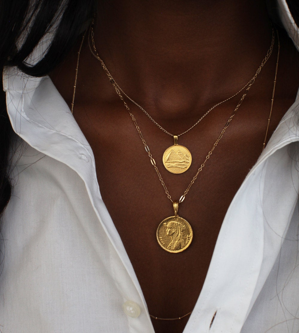 A woman models a stack of two necklaces from Omi Woods: a pyramid charm necklace and a Cleopatra coin pendant necklace